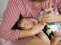 Asian mother`s arm wrapping around her crying baby girl`s face forcing the baby to take liquid medicine Royalty Free Stock Photo