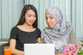Asian and muslim girls working on a laptop together Royalty Free Stock Images