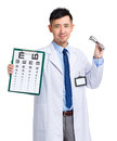 Asian oculist holding eye chart and glasses isolated on white Royalty Free Stock Image