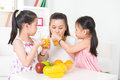 Asian parent and children drinking orange juice family happy enjoying cup of fresh squeeze fruit at home Stock Photos