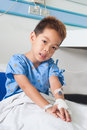 Asian patient boy with saline intravenous iv on hospital bed Stock Images
