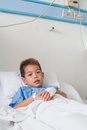 Asian patient boy with saline intravenous iv on hospital bed Royalty Free Stock Photos