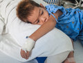 Asian patient boy with saline intravenous iv on hospital bed Royalty Free Stock Image