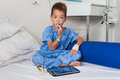 Asian patient boy with saline intravenous iv on hospital bed are using the tablet and eating medicines Royalty Free Stock Photo