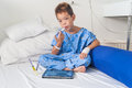 Asian patient boy with saline intravenous iv on hospital bed are using the tablet and eating medicines Stock Photos