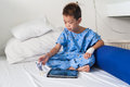 Asian patient boy with saline intravenous iv on hospital bed are using the tablet and eating medicines Stock Images