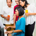Asian people sitting together piano having fun smiling Royalty Free Stock Photography