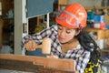 Asian pretty female carpenter using wood hammer. Royalty Free Stock Photo