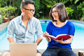Asian prosperous couple in the garden indonesian a tropical environment he is working she is reading a book Stock Image