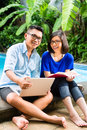 Asian prosperous couple in the garden indonesian a tropical environment he is working she is reading a book Stock Images