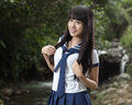 Asian schoolgirl standing in front of waterfall cute chinese with background Stock Photography