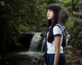 Asian schoolgirl standing in front of waterfall cute chinese with background Royalty Free Stock Photos