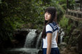 Asian schoolgirl standing in front of waterfall cute chinese with background Royalty Free Stock Images