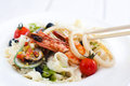 Asian seafood meal chopsticks using for eating closeup ingestion at chinese restaurant with traditional cutlery Stock Image