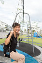 Asian senior citizen elderly woman is sitting on swing happily Royalty Free Stock Images