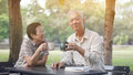 Asian senior couple start morning coffee in park, optimistic con Royalty Free Stock Photo