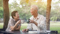 Asian senior couple start morning coffee in park, optimistic and Royalty Free Stock Photo