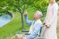 Asian senior man sitting on a wheelchair pointing Royalty Free Stock Photo