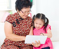 Asian senior woman and granddaughter women grandchild using tablet computer Stock Image