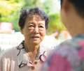 Asian senior women having conversation s at outdoor park candid shot Stock Image