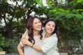 Asian sisters hugging and smiling in the park.