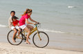 Asian sons and mother riding bicycle on beach tropical Stock Images