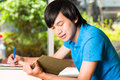 Asian student reading book or textbook learning young man sitting on sofa a Stock Photography