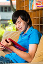 Asian student reading book or textbook learning young man sitting on sofa a Stock Images