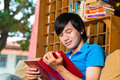 Asian student reading book or textbook learning young man sitting on sofa a Royalty Free Stock Images