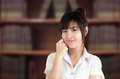 Asian student in uniform with blurry library background Royalty Free Stock Photo