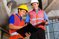 Asian supervisor and worker on building site chinese or controller or architect look a clipboard Stock Photography