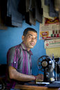 An asian tailor work on the sewing machine clothes hang on top engrossed with his Royalty Free Stock Image