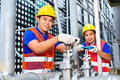 Asian technicians or engineers working on valve two a building technical equipment industrial site Royalty Free Stock Photo