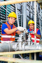 Asian technicians or engineers working on valve two a building technical equipment industrial site Royalty Free Stock Image