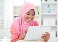 Asian teen using tablet pc computer southeast teenager at home muslim teenage girl living lifestyle Stock Photography