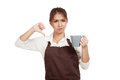 Asian waitress  in apron thumbs down with cup of coffee Royalty Free Stock Photo