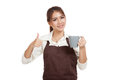 Asian waitress  in apron thumbs up with cup of coffee Royalty Free Stock Photo