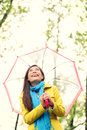 Asian woman in autumn happy with umbrella in rain female model looking up at clearing sky joyful on rainy fall day wearing yellow Stock Photos