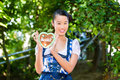 Asian woman with bavarian gingerbread heart young in traditional clothes or tracht a souvenir in beergarden on oktoberfest Stock Image
