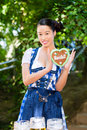 Asian woman with bavarian gingerbread heart young in traditional clothes or tracht a souvenir in beergarden on oktoberfest Royalty Free Stock Photos