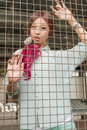 Asian woman behind a metal fence Royalty Free Stock Photo
