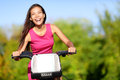 Asian woman on bike biking in city park bicycle happy girl cycling outdoors summer smiling of joy during outdoor activity Stock Photos