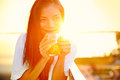 Asian woman drinking coffee in sun sitting outdoor sunshine light enjoying her morning smiling happy multiracial female Royalty Free Stock Photography