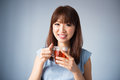 Asian woman drinking a cup of tea portrait wearing blue dress on blue background female model Royalty Free Stock Photography
