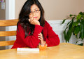 Asian woman in early forties sitting at table depressed relaxing dining with glass of juice sad or lonely expression Royalty Free Stock Photography