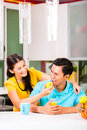 Asian woman feeding boyfriend with apple young couple handsome women after grocery shopping Royalty Free Stock Photography