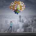 Asian woman flying with balloons young colorful over the cityscape Stock Photo