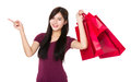 Asian woman hold with shopping bag and finger point upwards Royalty Free Stock Photo