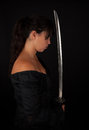 Asian woman holding her sword with a black background Royalty Free Stock Image