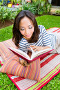 Asian woman at home in garden reading book young indonesian lying the and a her leisure time Stock Images